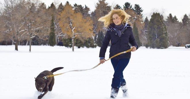 Kvinna springer och har kul med hund i snöig park
