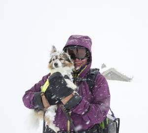 hund i famnen på matte i skidutrustning och oj vad det snöar!