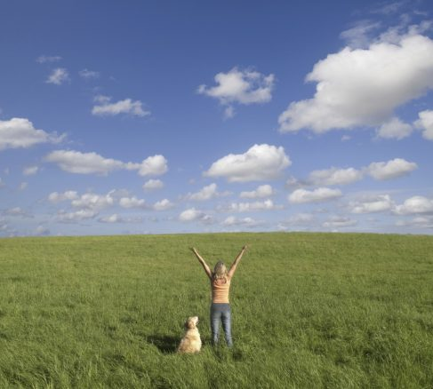 kvinna med hund på fält som lyfter sina armar mot skyn