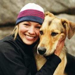 Kvinna med mössa i 30-årsåldern kramar hund