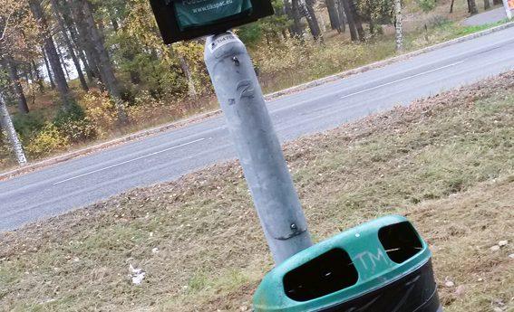 Stolpe med hundbajspåsstation och reklamplats för lokala företag, samt en skräpkorg